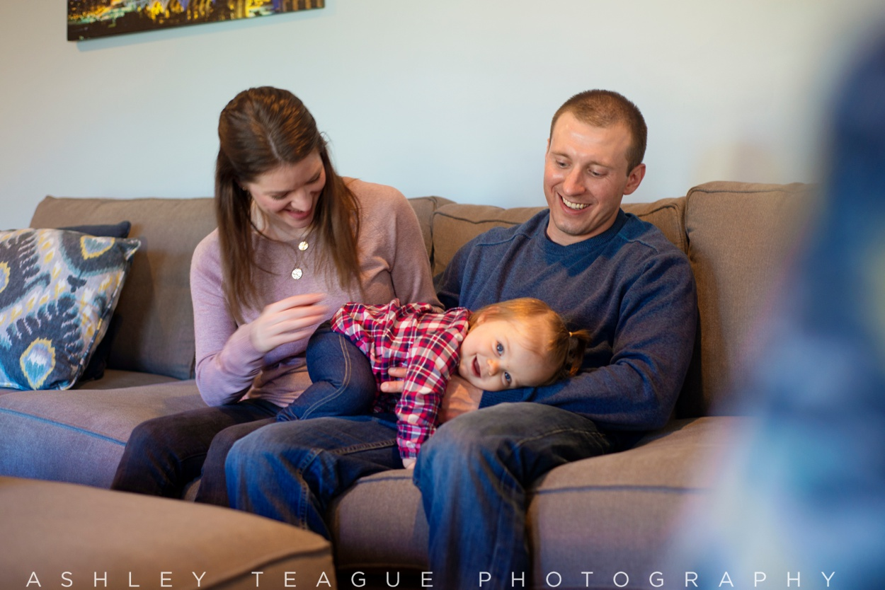 Young Family Laughing on Couch