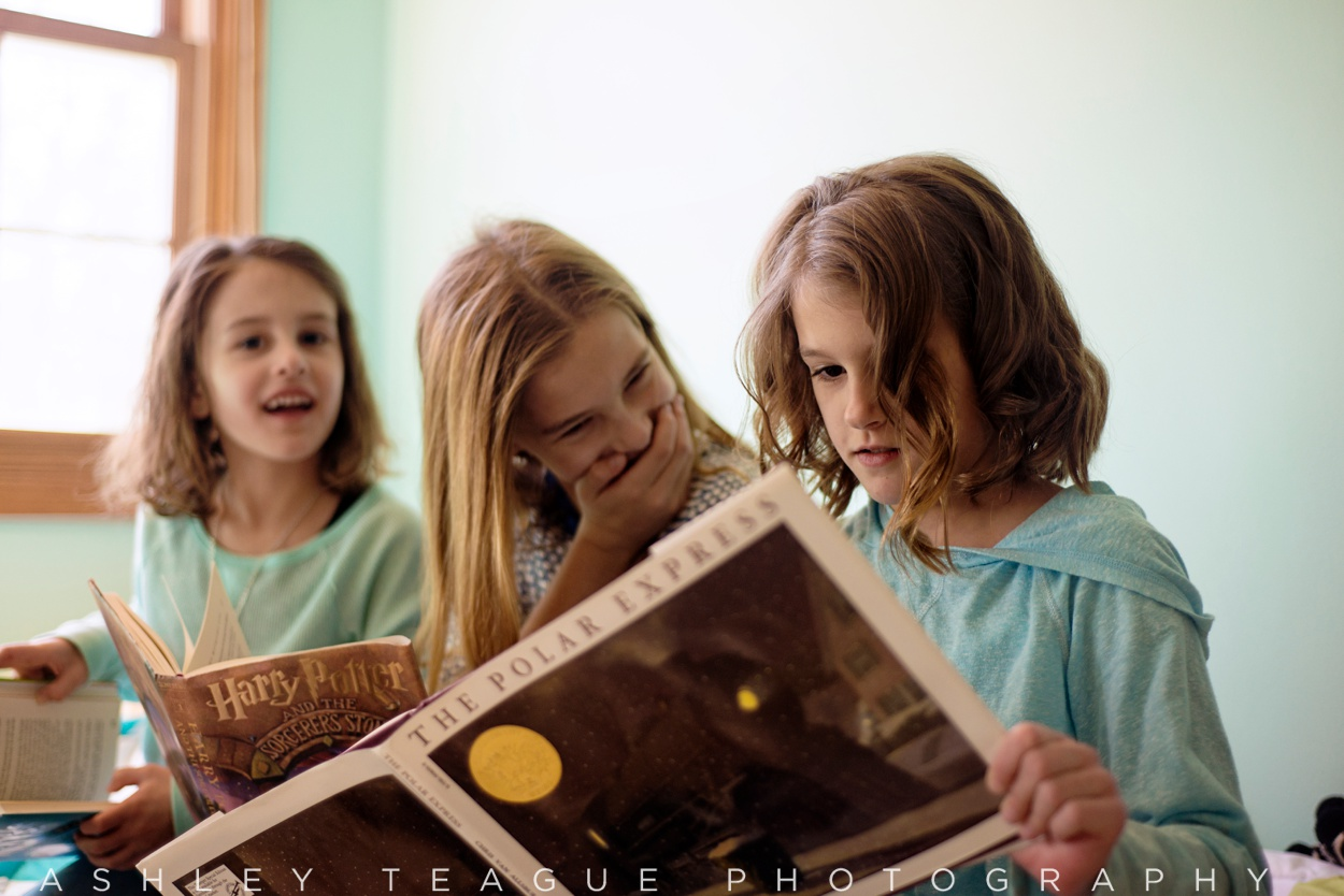 Young Girl Laughing At Sister Reading